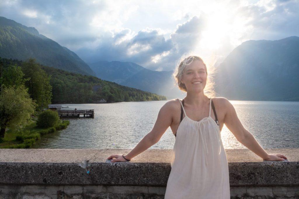 Pernille Hjerpeseth i sommerkjole foran et vann i solnedgang