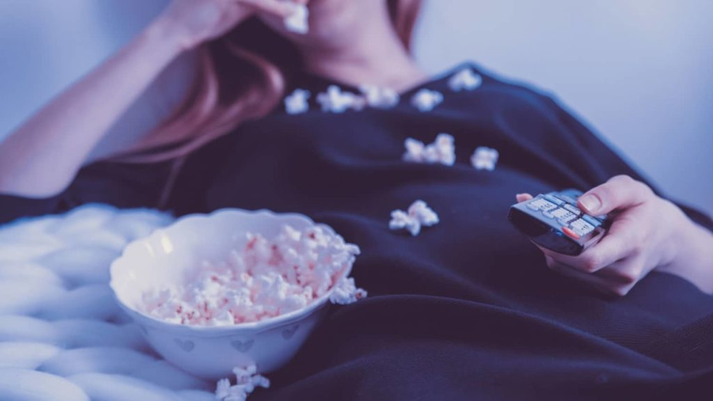Kvinne ligger på sofaen med en fjernkontroll i hånden og spiser popcorn fra en bolle med den andre hånden