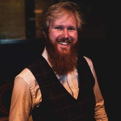 Lars Magnus smilende foran en mørk bakgrunn