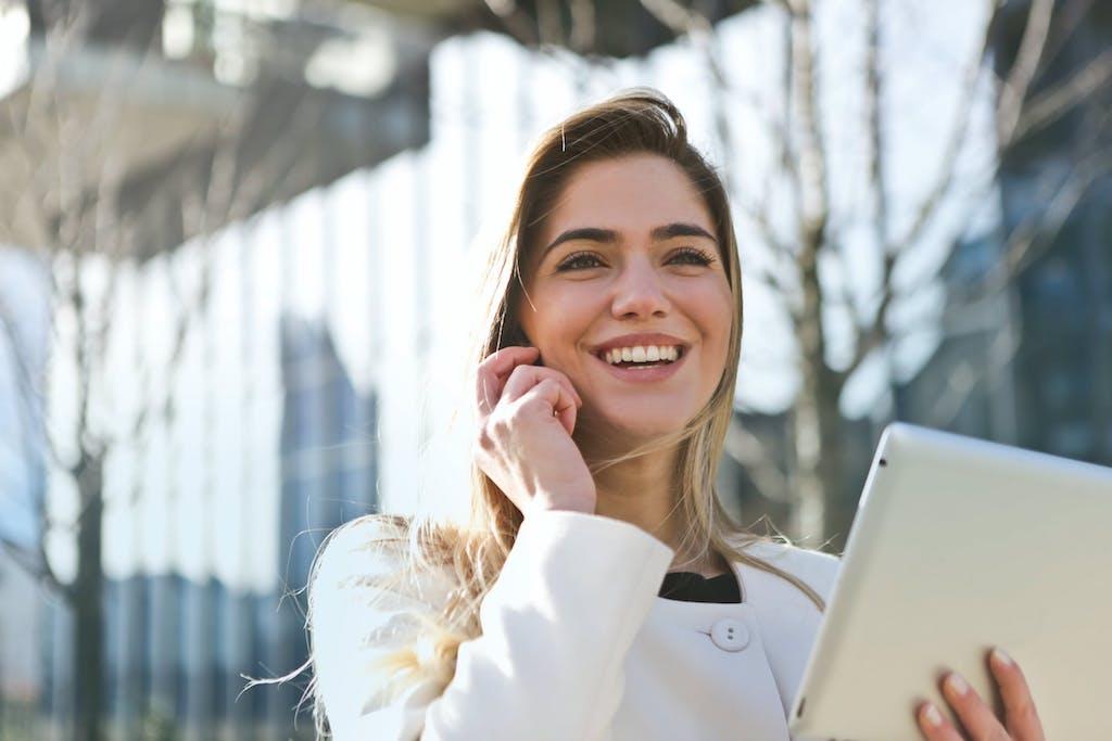 En smilende jente ute foran et glassbygg