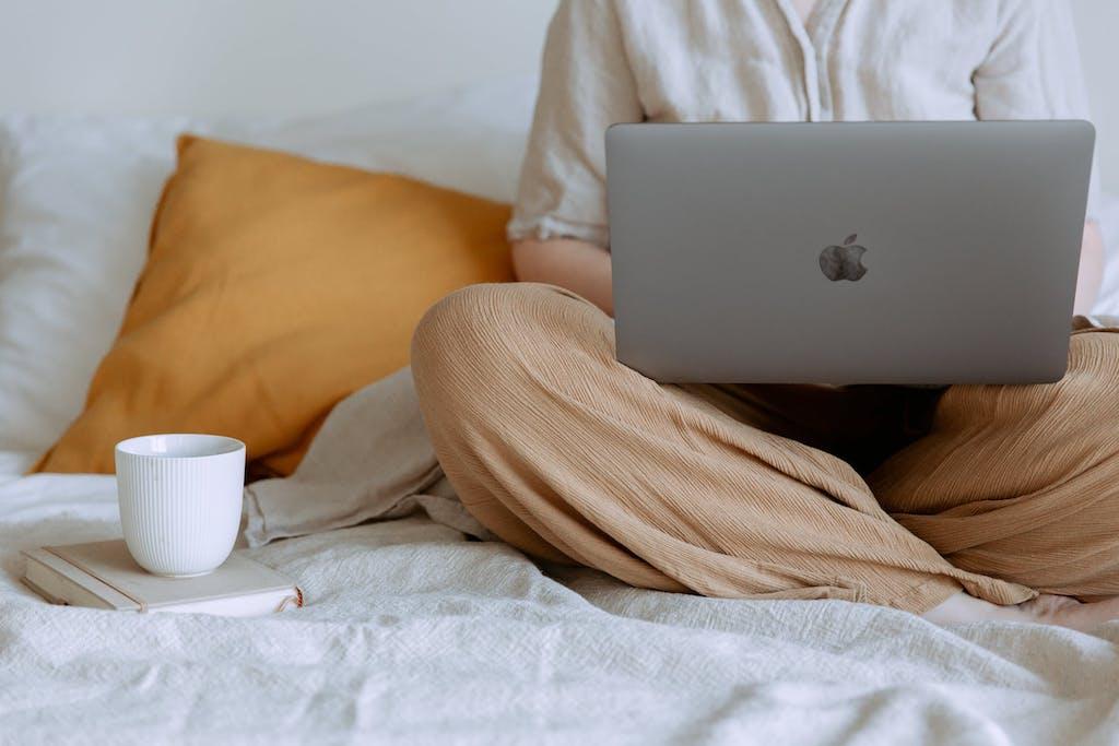 Nært bilde av fanget til en student som sitter i sengen sin med MACen på fanget og en kaffekopp