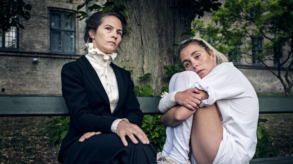 To damer i barokk antrekk ser melankolsk utover intet